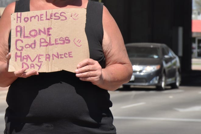 A woman holds a cardboard sign while standing in the median on the west side of the intersection at Southwest Drive and Winters Freeway on Friday.