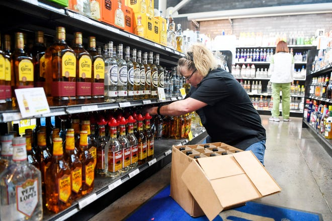 Marti Gregg stocks bottles of tequila at the ABC Store on Tunnel Road in Asheville March 28, 2019.