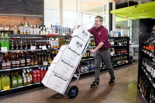 Jonathan Bass, manager of the ABC Store on Tunnel Road, moves boxes of liquor as a new shipment is stocked March 28, 2019 in Asheville.