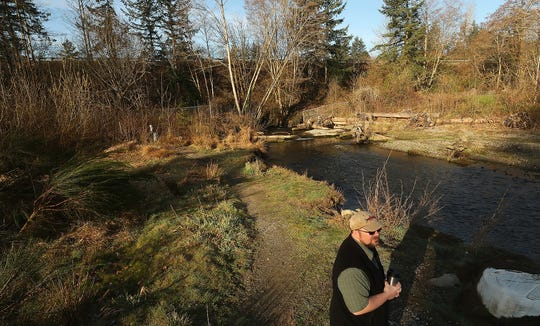 Washington Department of Fish and Wildlife's Chris Waldbillig stands along the mouth of Chico Creek as he talks about how a new bridge would restore the natural stream flow of Kitsap's most-productive salmon run.