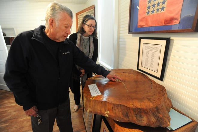 In the archive room at Tabernacle United Methodist Church, Robert Goodson shows pastor Lisa Beth White the center growth ring on a section of a hemlock tree that used to mark the grave of Coleman Stepp.