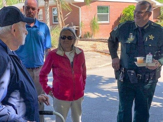 Longtime Meals on Wheels volunteer Ed Kydd, 102, left, chats with Josh Jensen, president and CEO of Aging Matters in Brevard; Kydd's daughter, Janet von Berg, who delivers meals with her father; and Sheriff Wayne Ivey, honorary chairman of this year's March for Meals campaign.