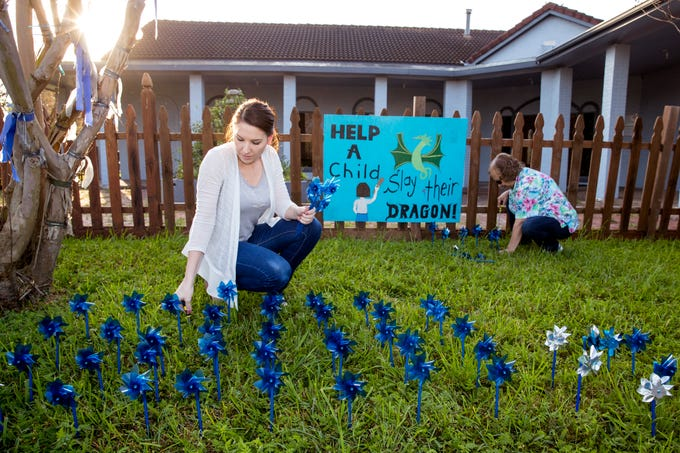 Kimberly Beck (left) and Delia Lopez help install pinwheels in front of CASA of the Coastal Bend on Friday, March 29, 2019. The 1,066 pinwheels represent a child from the Coastal Bend who was in foster care last year and will stay up throughout the month of April, which is Child Abuse Awareness Month.