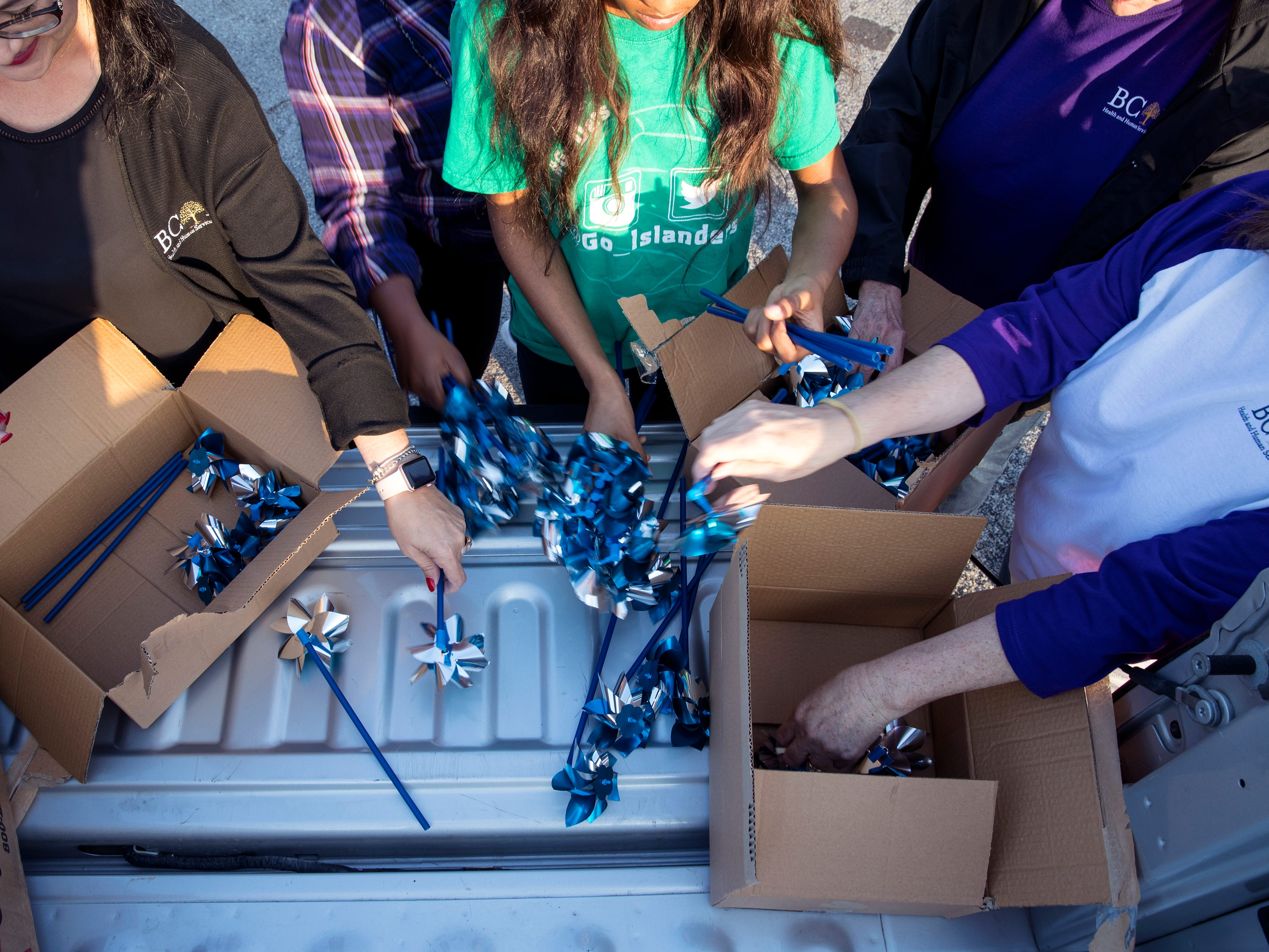 Marissa Cano (left) and others assemble pinwheels to be installed in front of CASA of the Coastal Bend on Friday, March 29, 2019. The 1,066 pinwheels represent a child from the Coastal Bend who was in foster care last year and will stay up throughout the month of April, which is Child Abuse Awareness Month.