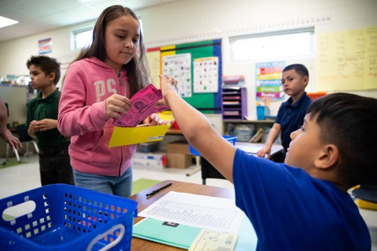 Hicks Elementary student Serenity Martinez pays her taxes during the school's Minitropolis program on Friday, March 29, 2019. The Minitropolis program is to teach students social and financial skills.
