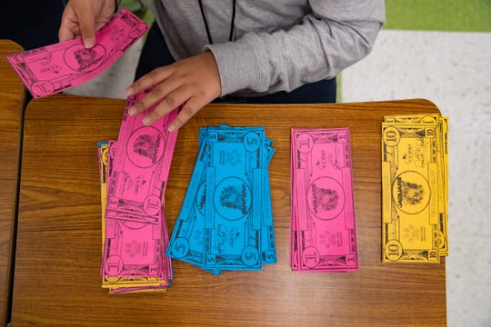 Hicks Elementary student Daniel Salinas counts jaguars dollars in the toy store during the school's Minitropolis program on Friday, March 29, 2019. The Minitropolis program is to teach students social and financial skills.