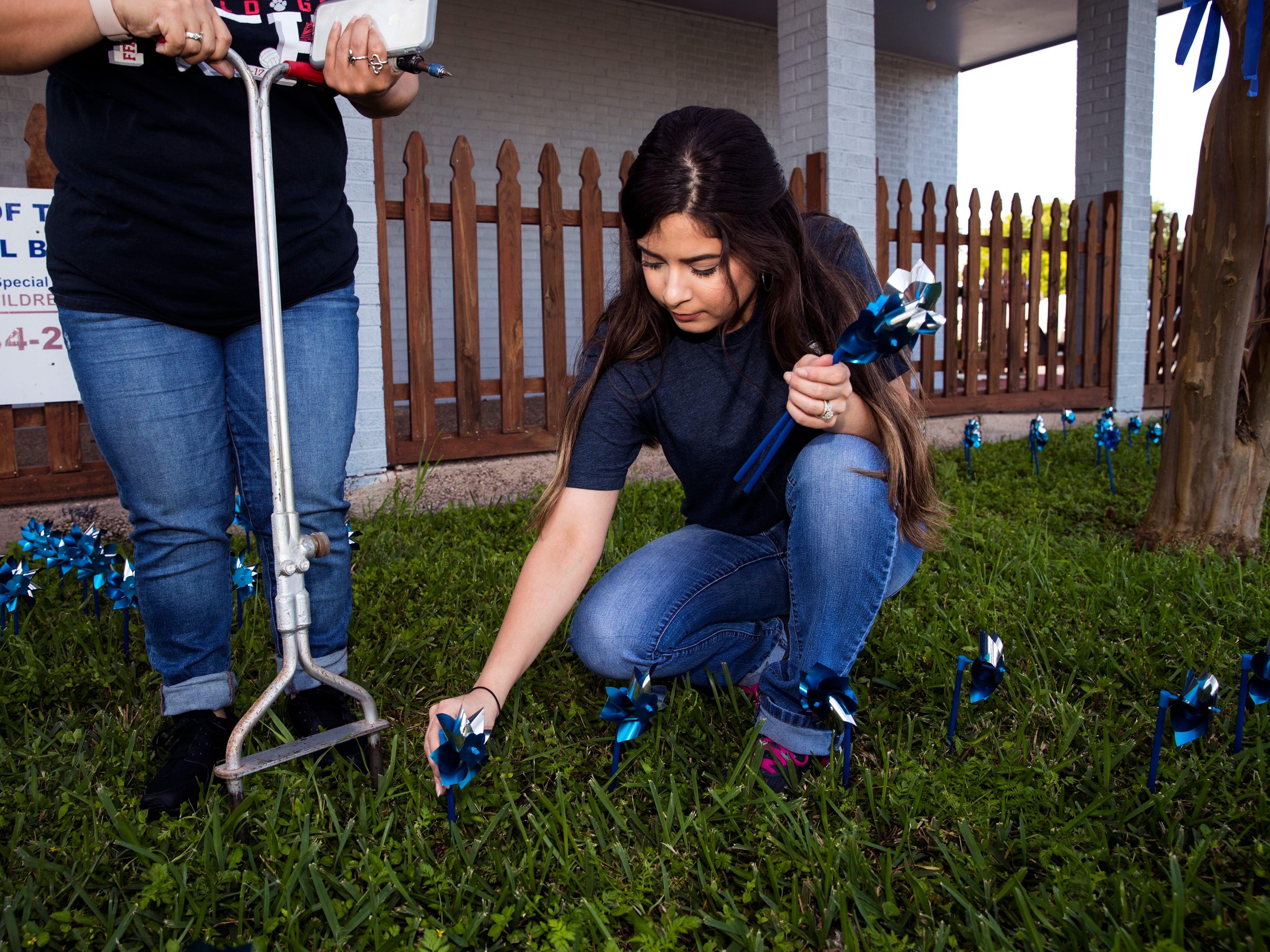 Kristal Valdez helps install pinwheels in front of CASA of the Coastal Bend on Friday, March 29, 2019. The 1,066 pinwheels represent a child from the Coastal Bend who was in foster care last year and will stay up throughout the month of April, which is Child Abuse Awareness Month.