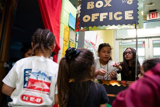 Hicks Elementary students Sadye Orgas and Mia Comer sell movie tickets during the school's Minitropolis program on Friday, March 29, 2019. The Minitropolis program is to teach students social and financial skills.