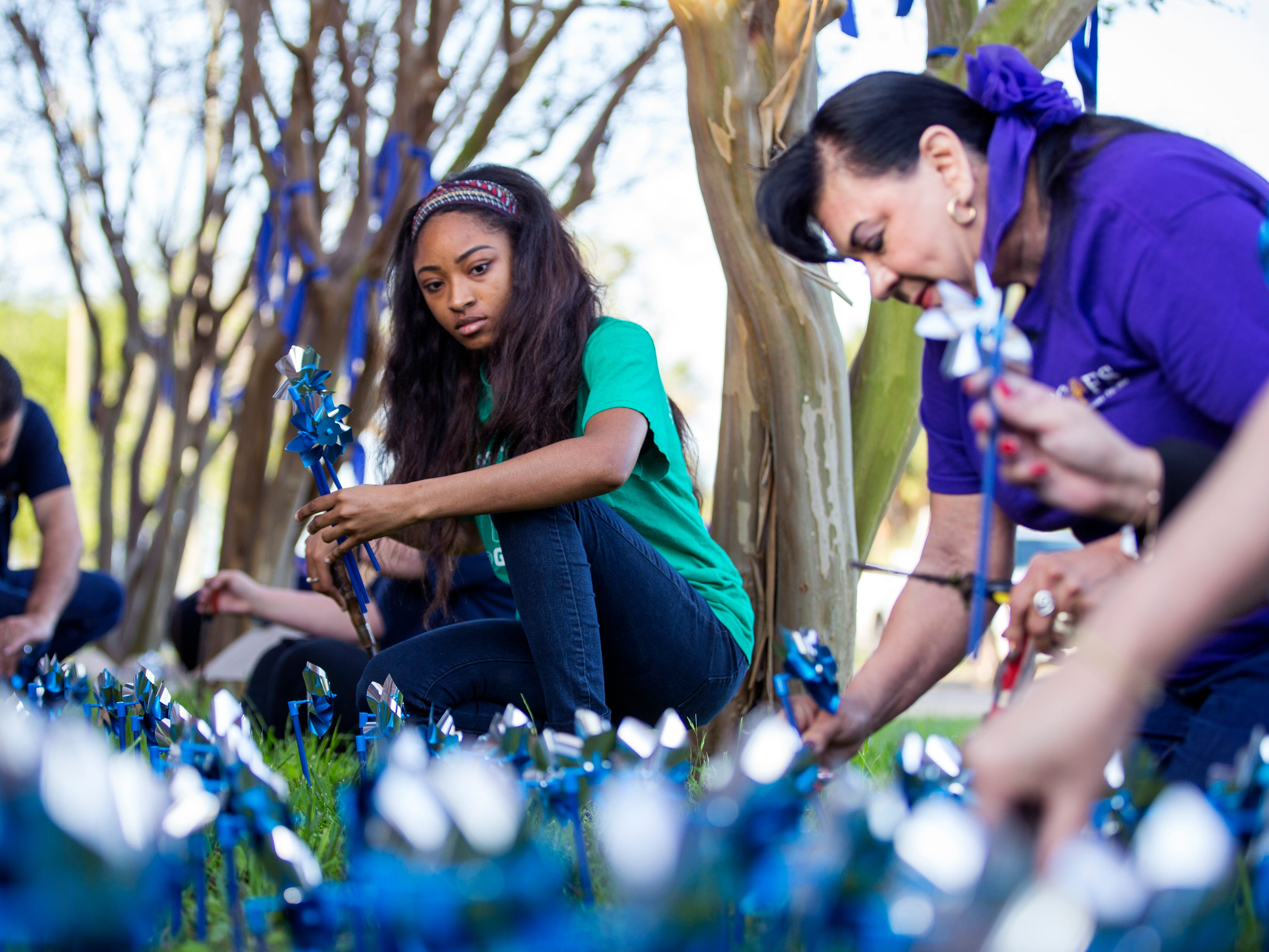 Alesha Norris (center) help install pinwheels in front of CASA of the Coastal Bend on Friday, March 29, 2019. The 1,066 pinwheels represent a child from the Coastal Bend who was in foster care last year and will stay up throughout the month of April, which is Child Abuse Awareness Month.