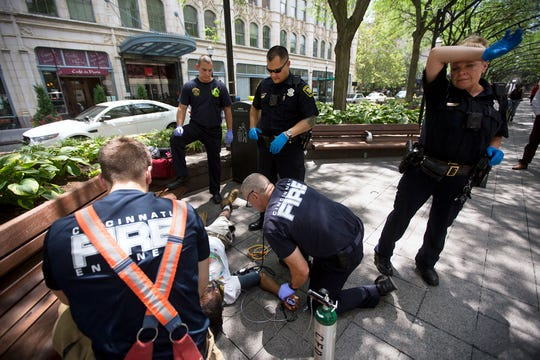 Cincinnati first responders tend to an overdose victim at Piatt Park downtown in July 2017. Police administer one nasal naloxone dose first, then paramedics use additional, IV naloxone to revive the man. He rejects further treatment and walks away.