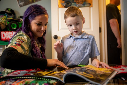 Monster Jam Driver Kayla Blood shows Brendan Hogan her picture in the Monster Jam program Friday, March 29, 2019 in Batavia, after revealing his new Monster Jam themed room to him.