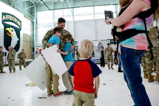 A father returning home from deployment with the 101st Airborne Division embraces his sons at Hangar 3 in Fort Campbell, Kentucky, on Thursday, March 28, 2019.