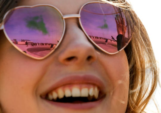 Kirsten Yeager smiles and looks out for her brother with another visitor's hand reflected in her glasses at Hangar 3 in Fort Campbell, Kentucky, on Thursday, March 28, 2019.