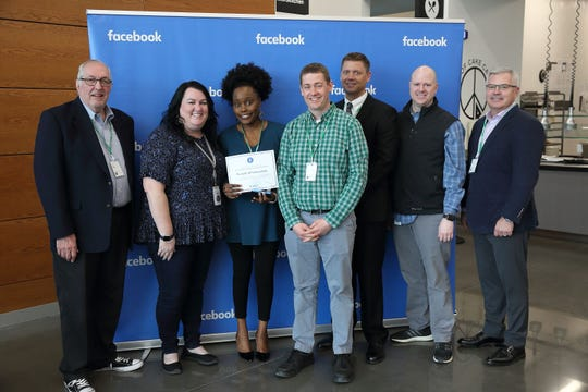 "Pursuit of Innovation representatives accept a $10,000 grant from Facebook for its ""Building the Tech Pipeline"" program, which connects students with local tech businesses where they can learn, network and job shadow."
