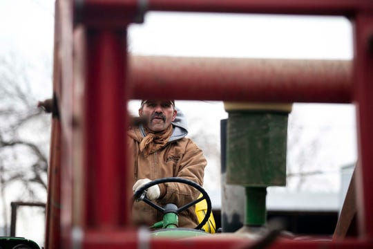 Bob Blum pulls donated bales of hay off a truck to be stored on his farm before being distributed to farmers impacted by flooding, on Thursday, March 28, 2019, near Malvern.