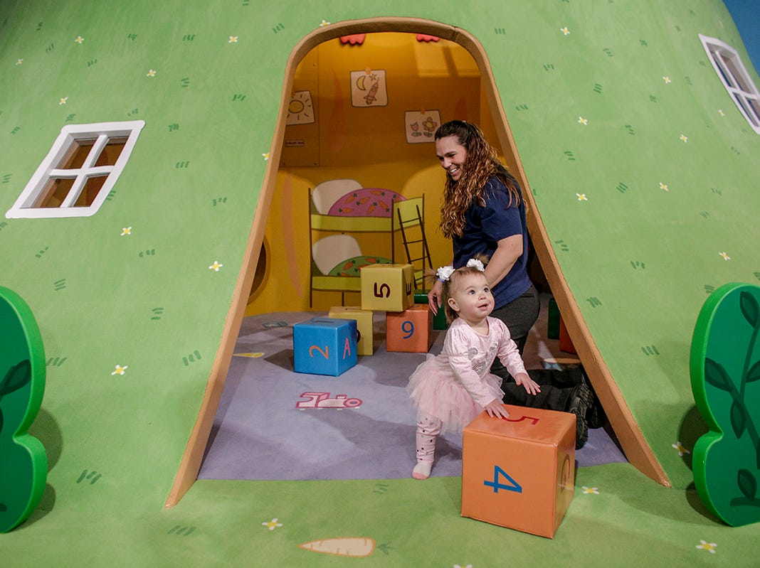 Michelle Koons, 41, follows her daughter, Ashlee Eggleston, 1, both of Waterford into Rebecca Rabbit's Underground Adventure play area at Peppa Pig World of Play attraction at Great Lakes Crossing in Auburn Hills, Mich. photographed on Friday, March 29, 2019.