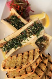 Roasted bone marrow is topped with a mixture of oregano, capers and chiles at Michael Symon's Roast in Detroit.