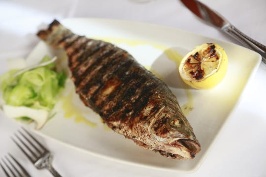 Whole grilled branzino is served with ribbons of celery and shaved trumpet mushrooms at Michael Symon's Roast in Detroit.
