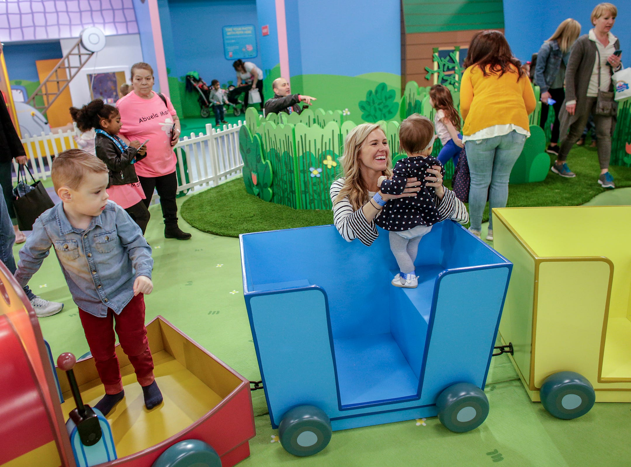 Shawna Coscarelli, 32, holds up her daughter, Ella, 1, while playing on a train in the sensory garden with her son, Austin, 3, at Peppa Pig's World of Play attraction at Great Lakes Crossing in Auburn Hills, Mich. photographed on Friday, March 29, 2019.