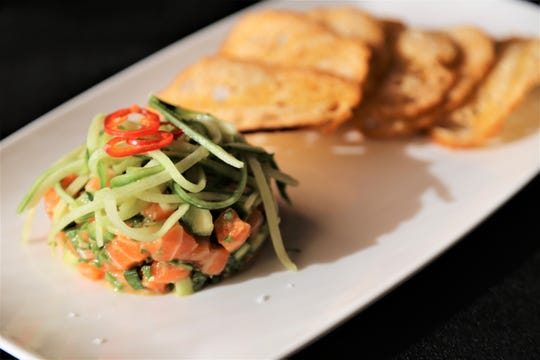 Ora King salmon tartare from Michael Symon's Roast in Detroit is topped with cucumber dressed in a sesame-soy sauce and served alongside paper-thin crisps of Zingerman's sourdough.