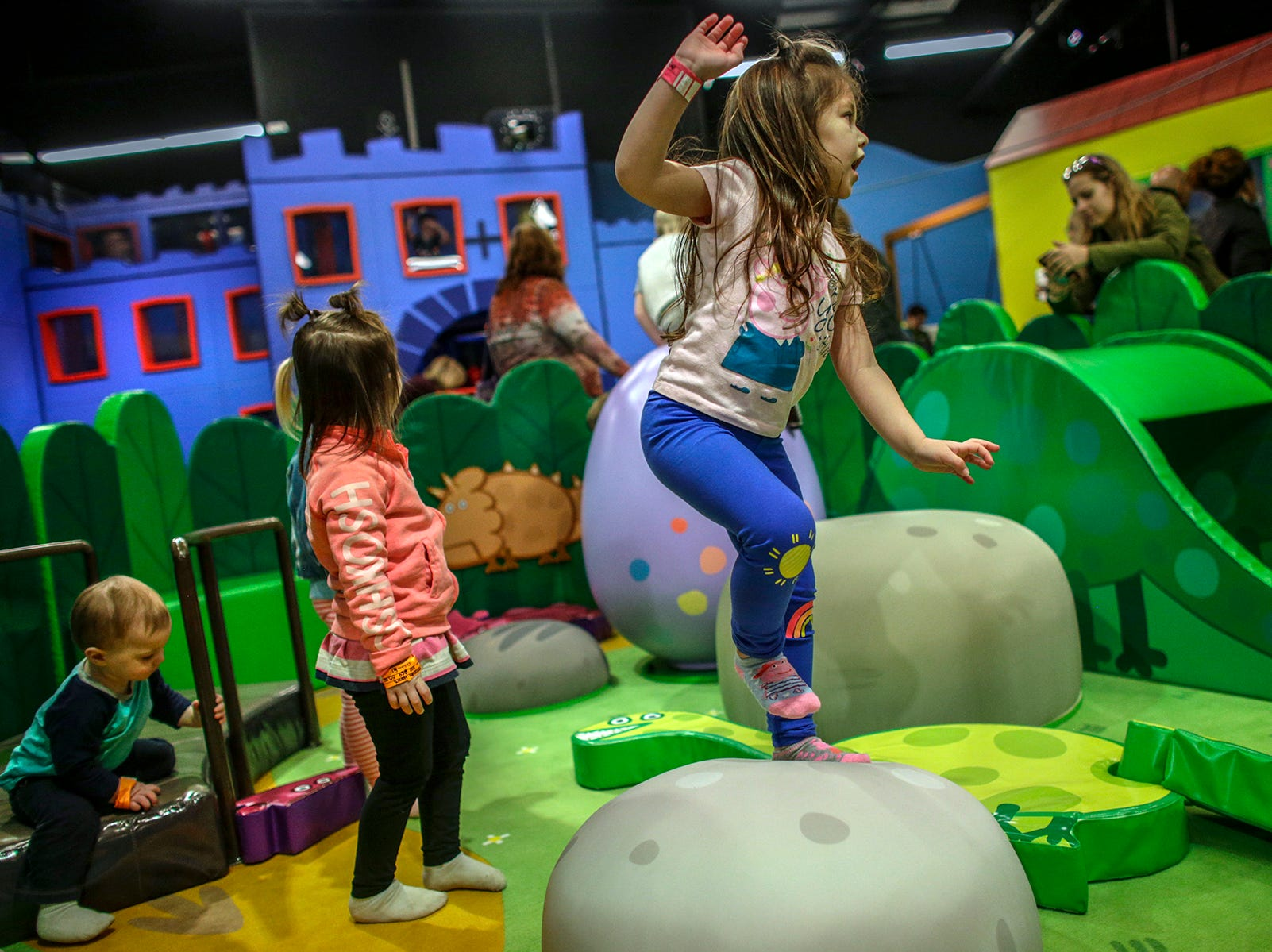Ayla Aquino, 4, of Bruce Twp, Mich. stands on a rock pillow in George's Dinosaur Discovery play area at Peppa Pig World of Play attraction at Great Lakes Crossing in Auburn Hills, Mich. photographed on Friday, March 29, 2019.