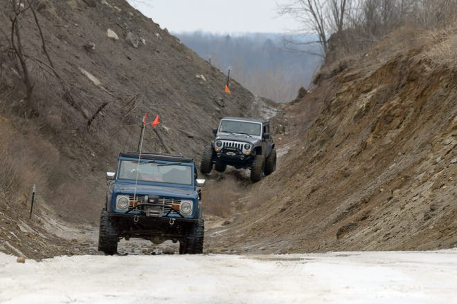 Off-roaders rumble through a gully on a trial run on Feb. 23 at a park planned for them in north Oakland County.