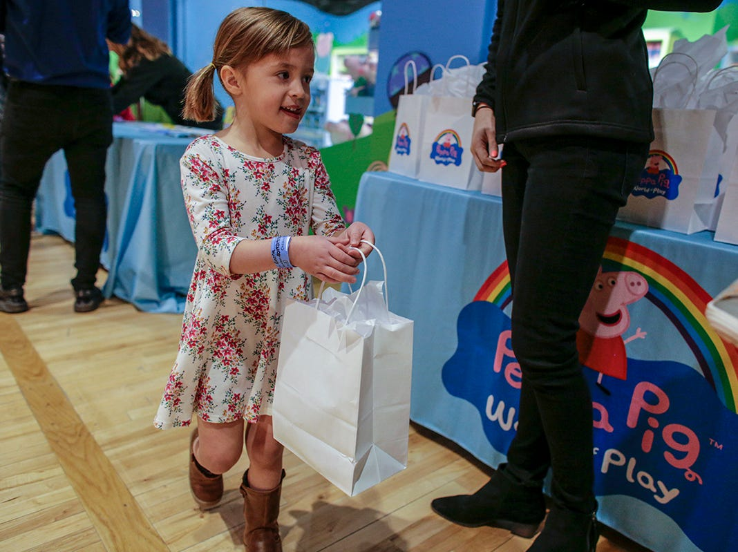 Emma Ramsay, 4, of Waterford, Mich. receives a gift bag at the preview of Peppa Pig World of Play attraction at Great Lakes Crossing in Auburn Hills, Mich. photographed on Friday, March 29, 2019.