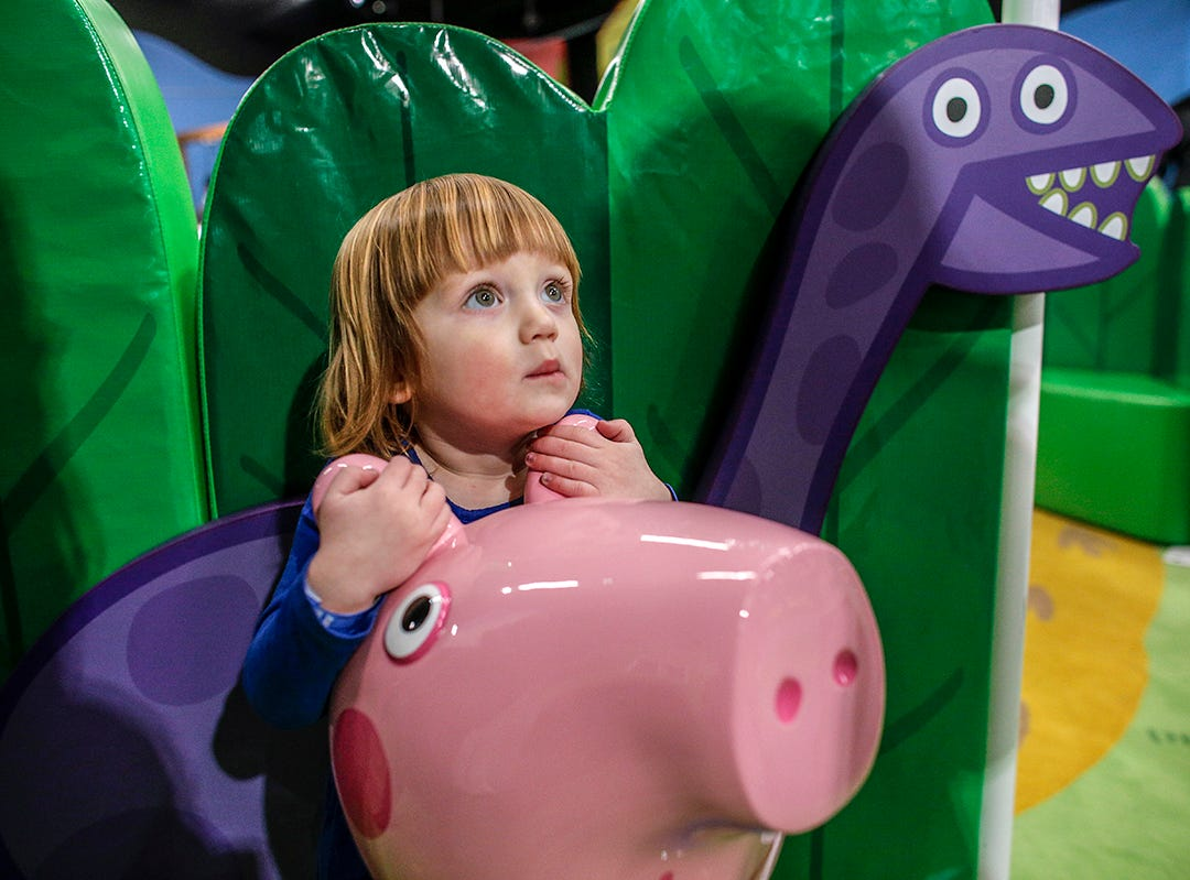 Frances Mossine, 4, of Ferndale hugs a life-size replica of George in front of George's Dinosaur Discovery play area at Peppa Pig World of Play attraction at Great Lakes Crossing in Auburn Hills, Mich. photographed on Friday, March 29, 2019.