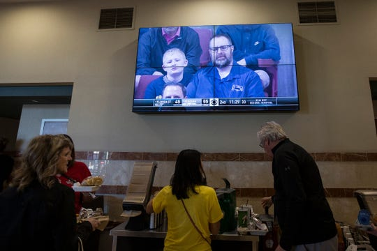 A TV screen on the concourse level of Honda Center shows Gregg Nigl and his son Kaiden Nigl, 9, both of Columbus, Ohio, as they watch the Gonzaga-Florida State game in Anaheim, Calif., Thursday, March 28, 2019.