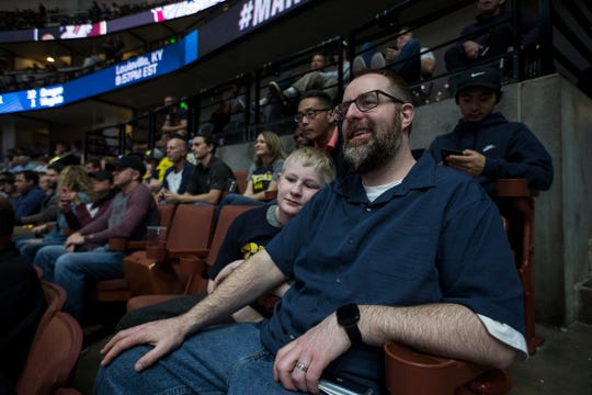 Michigan fan Gregg Nigl and his son Kaiden Nigl, 9, both of Columbus, Ohio, watch the Gonzaga-Florida State game at the Honda Center in Anaheim, Calif., Thursday, March 28, 2019. Gregg Nigl is the first person to correctly pick every winner in the first two rounds of the NCAA tournament.