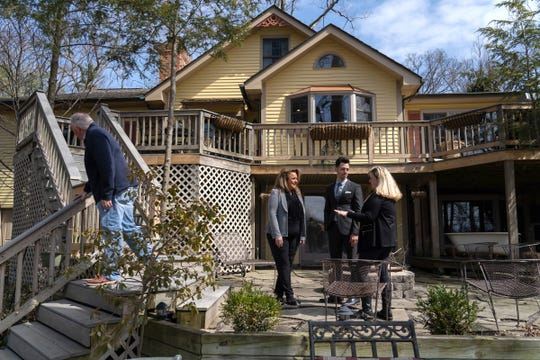 Realtor Susan Vogel (center) and her business partner RJ Helguera talk with Elizabeth Button of Troy on the back deck of a home for sale in Shelby Township on Friday, March 29, 2019 as her husband Mark Harrison of Troy looks over the yard.