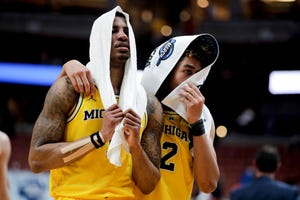Michigan guard Charles Matthews, left, and guard Jordan Poole leave the court after the team's 63-44 loss to Texas Tech.