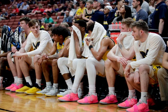 Michigan players watch from the bench during the second half against Texas Tech.