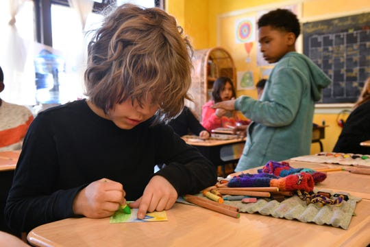 Third grader Pfeiffer Atwood, 9, of Detroit works on a hand-drawn postcard to send to students at other Waldorf schools around the world.