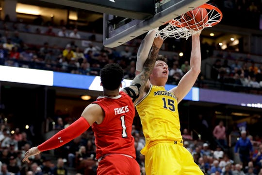 Michigan center Jon Teske dunks next to Texas Tech guard Brandone Francis during the first half of their NCAA Tournament game.
