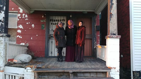 Three officials with MuslimARC -- Namira Islam, executive director, Hazel Gomez, board member, and Margari Hill, managing director -- stand in front of the Detroit house the group plans to renovate to become its Michigan headquarters.