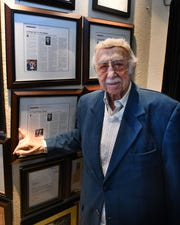 Jewish News restaurant columnist Danny Raskin, 100, stands beside some of his work, which hangs on the walls of Steven Lelli's Inn on the Green restaurant in Farmington Hills.