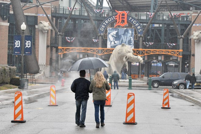 Tiger fans wander outside Comerica Park after the Opening Day game in 2018 was postponed due to rain. There are showers in the forecast for this year's home opener Thursday.