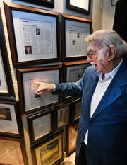 Jewish News restaurant columnist Danny Raskin, 100, looks at one of his columns which hangs on the walls of Steven Lelli's Inn on the Green restaurant in Farmington Hills.