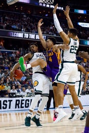 LSU guard Skylar Mays (4) loses control of the ball as he goes up against Michigan State forwards Xavier Tillman (23) and Kenny Goins (25) during the first half.