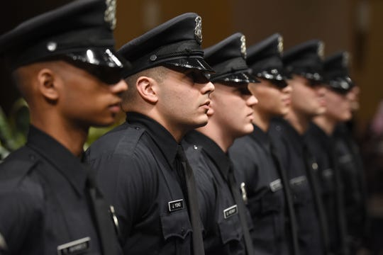 Newly sworn-in Detroit police officers participate in their graduation ceremony  on March 29. Departments across Metro Detroit are having a tough time hiring police officers, particularly minorities.