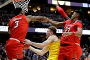 Michigan forward Ignas Brazdeikis, middle, drives to the basket between Texas Tech forward Deshawn Corprew, let, and guard Jarrett Culver .