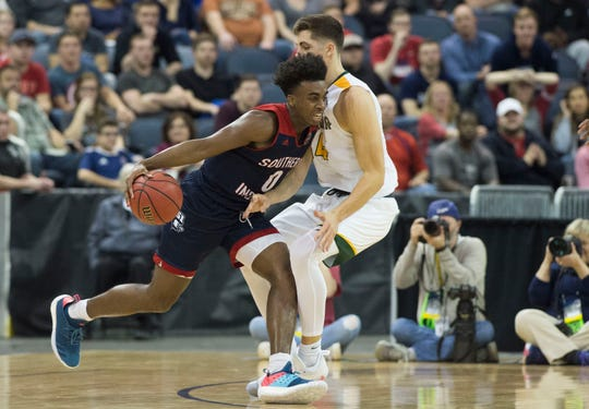 University of Southern Indiana's Kobe Caldwell (0) drives past Point Loma's Jack Hutchison (4) during the NCAA Division II Final Four men's basketball tournament at Ford Center in Evansville, Ind., Thursday, March 28, 2019.