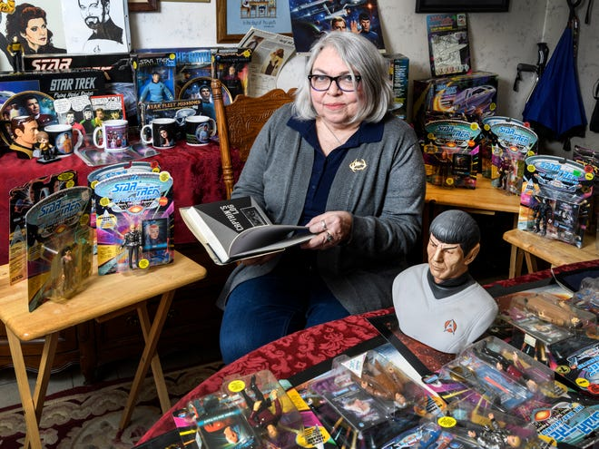 """Trekkie"" Shelba Bauermeister shows off an assortment of Star Trek memorabilia she has collected over the years, including the book she is holding called ""Star Trek Memories"" written by William Shatner, at her home in Evansville, Ind., Thursday, March 28, 2019. Shatner is coming to Evansville's Victory Theatre, Wednesday night, April 3, to screen the classic film ""Star Trek II: The Wrath of Khan,"" before tell stories and take questions from audience members."