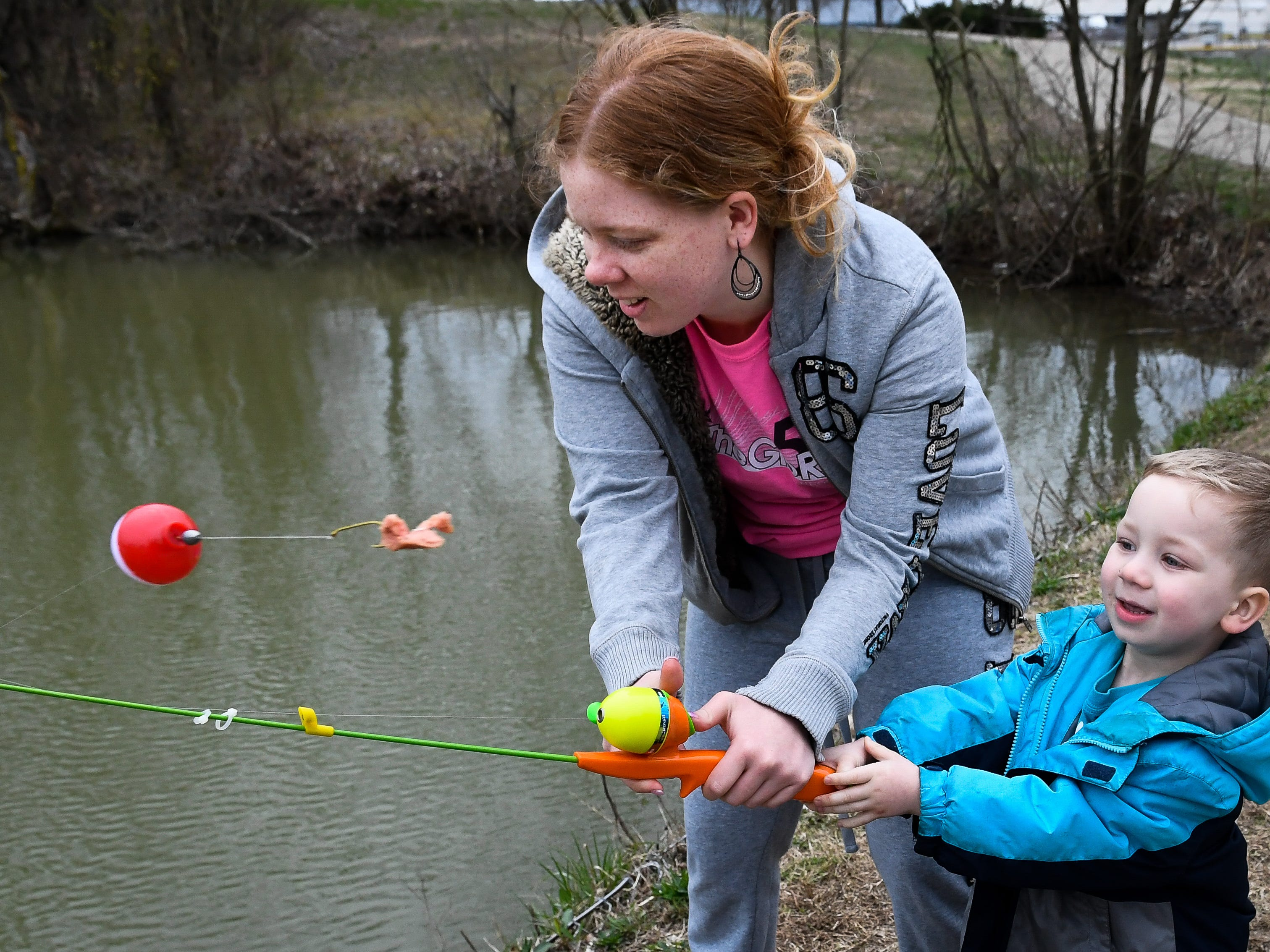 Mastering the art of the cast, Yesenia Deleon helps Kayden Kress, three years-old, launch his piece of hotdog out into the lake at Evansville's Garvin Park during a family fishing trip Friday on the last day of spring break, March 29, 2019.