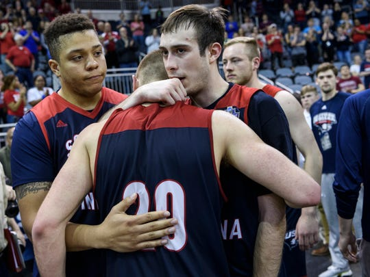University of Southern Indiana's Tyler Dancy (31) and Nate Hansen (5) embrace Alex Stein (20) following their team's ten-point loss to the Point Loma Sea Lions in the NCAA Division II Final Four men's basketball tournament at Ford Center in Evansville, Ind., Thursday, March 28, 2019. The Screaming Eagles fell to the Sea Lions, 81-71.