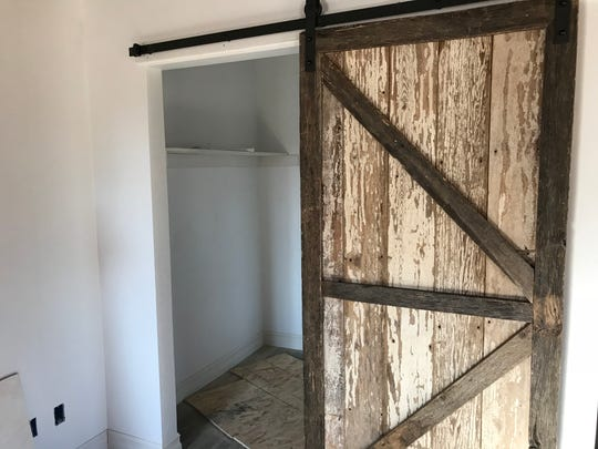 Keeping with the rustic feel of the apartments, a bar door covers the walk-in closet in the Livery Lofts.