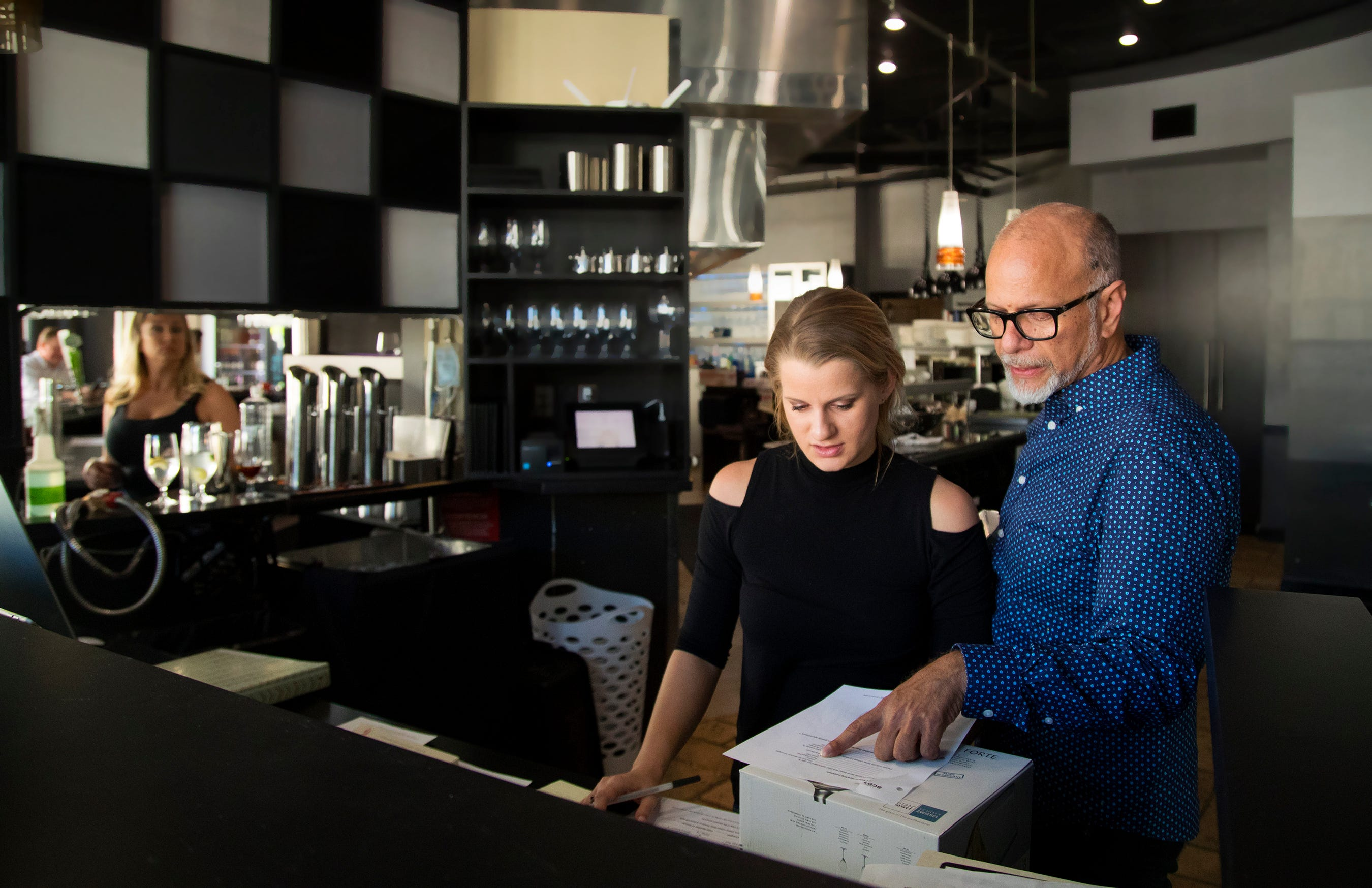 Joelle Findley and Cesar Otero, of Cru restaurant at Bell Tower Shops in south Fort Myers, prepare for customers on Friday. Cru is closing permanently in late April.