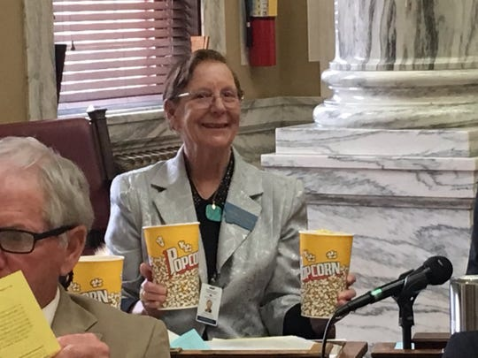 Rep. Bridget Smith, D-Wolf Point, is treated to popcorn courtesy of Rep. Gordon Pierson, D-Deer Lodge, after a film tax credit bill she backs passed second reading in the House. The bill is sponsored by Rep. Wylie Galt, R-Martinsdale.