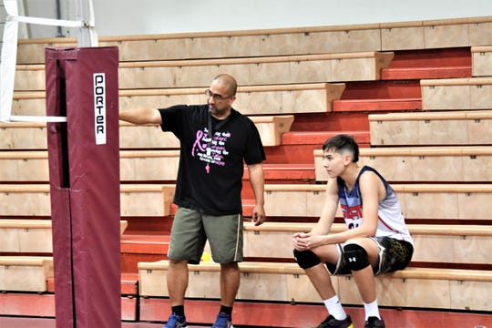 Father Duenas Friars coach Steve Pangelinan offers some tips on court movement and defensive coverage to Matthew Fegurgur during high school volleyball practice March 28 at the Jungle.